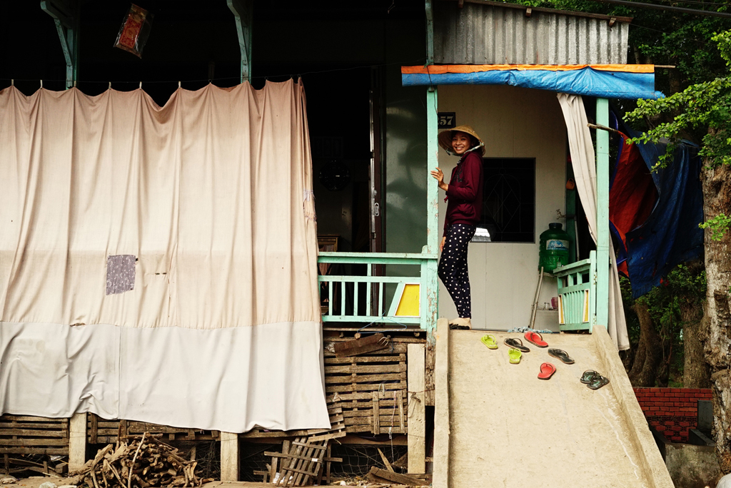 10.Girl standing with a smile on her stilt house's porch