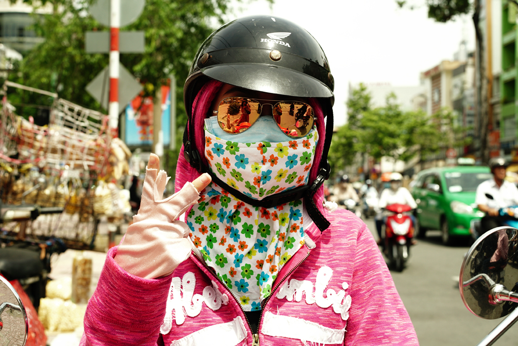 Girl with a colorful and flowery %22Cover-up Style%22 driving on the streets of H.C.M.C., June 2015