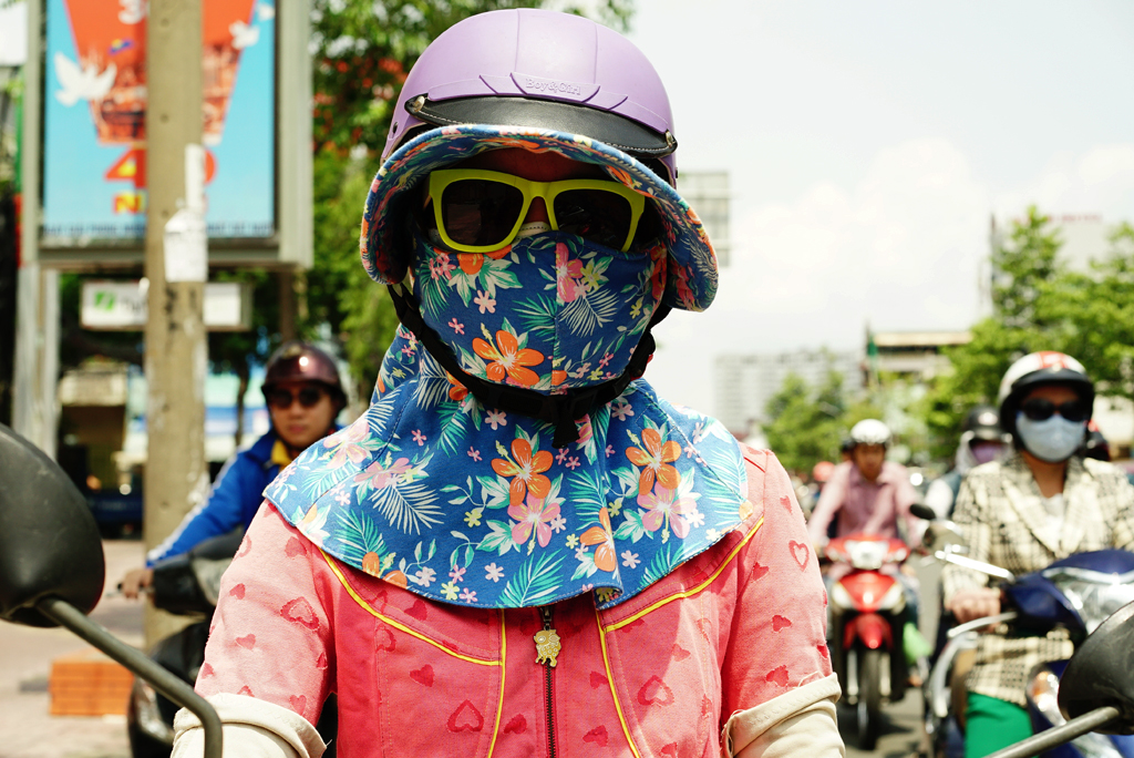 Girl with a colorful flowery %22Cover-up Style%22 driving on the streets of H.C.M.C., June 2015