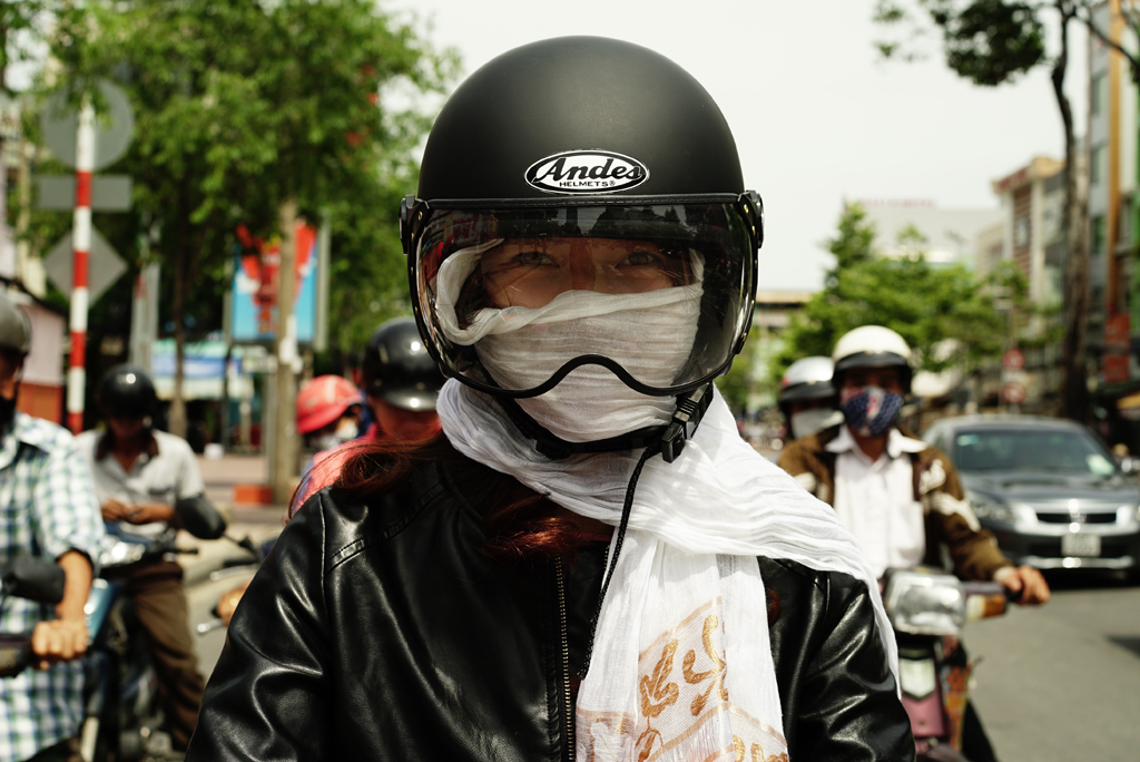 Girl with a modern leather motorcicle %22Cover-up Style%22 driving on the streets of H.C.M.C., Vietnam, June 2015