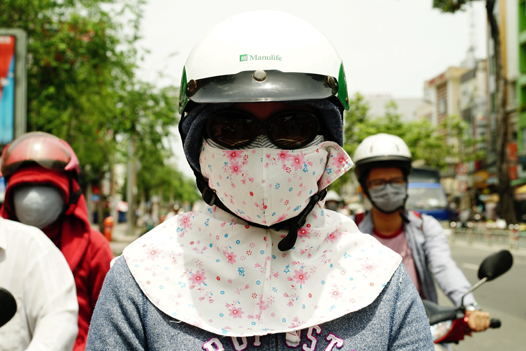 Girl with a white flowery %22Cover-up Style%22 driving on the streets of H.C.M.C., Vietnam, June 2015