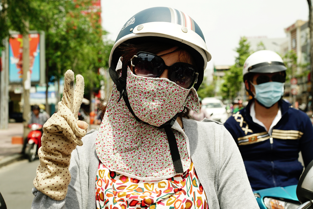 Girl with gloves and flowery %22Cover-up Style%22 driving on the streets of H.C.M.C., Vietnam, June 2015