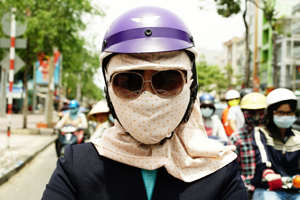 Girl with jacket and pinky %22Cover-up style%22 driving on the streets of H.C.M.C., Vietnam, June 2015