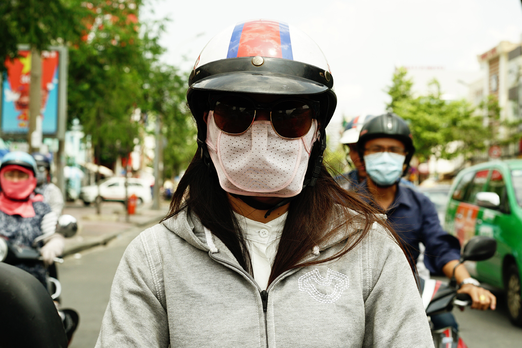 Girl with pig mask %22Cover-up style%22 driving on the streets of H.C.M.C., Vietnam, June 2015