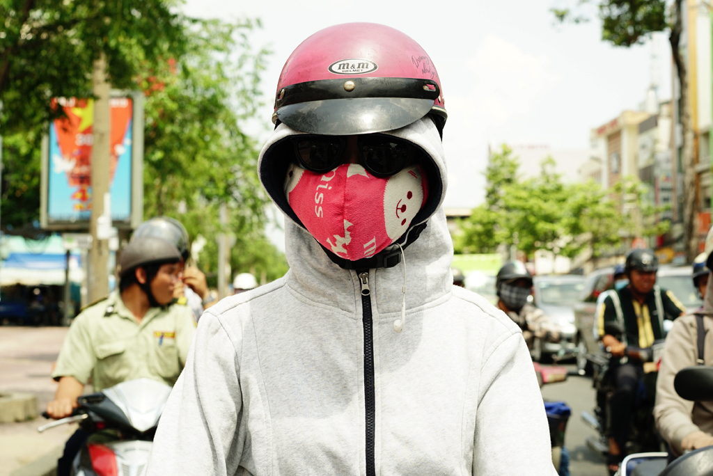 Teen-ager with a pink mask and gray sweater %22Cover-up Style%22 driving on the streets of H.C.M.C., Vietnam, June 2015