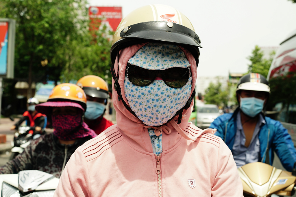 Teen-ager with a pink sweater and flowery mask %22Cover-up Style%22 driving on the streets of H.C.M.C., Vietnam, June 2015