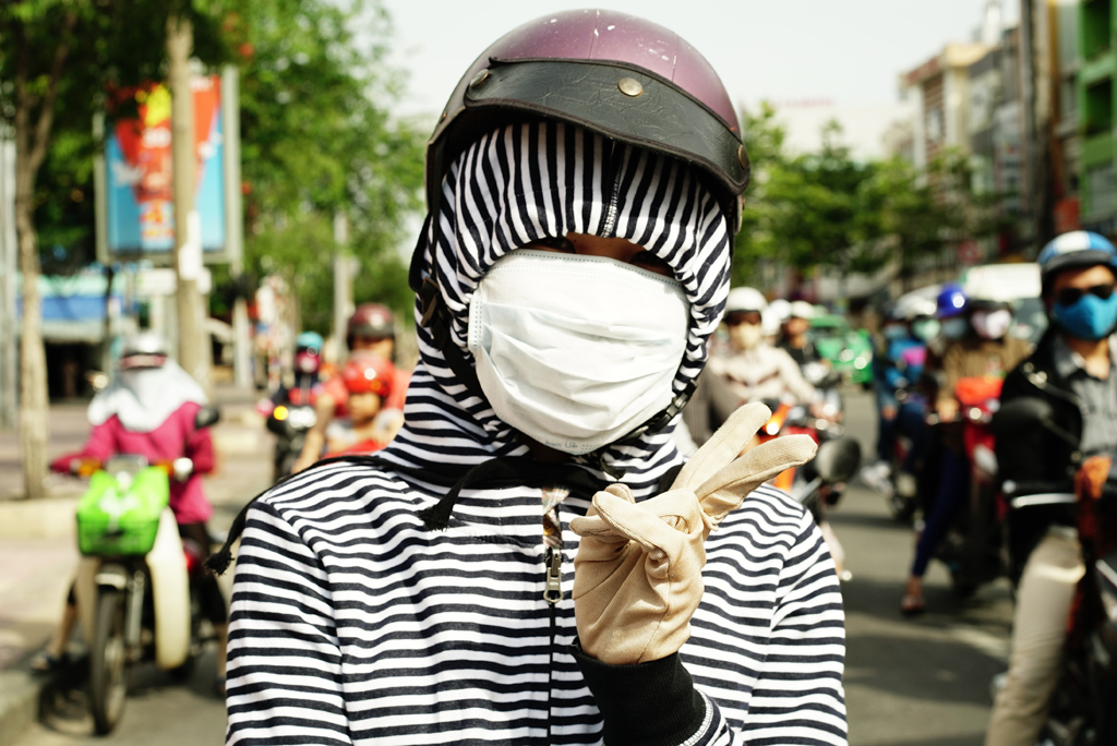 Teen-ager with black and white strips sweater %22Cover-up Style%22 driving on the streets of H.C.M.C., vietnam, June 2015