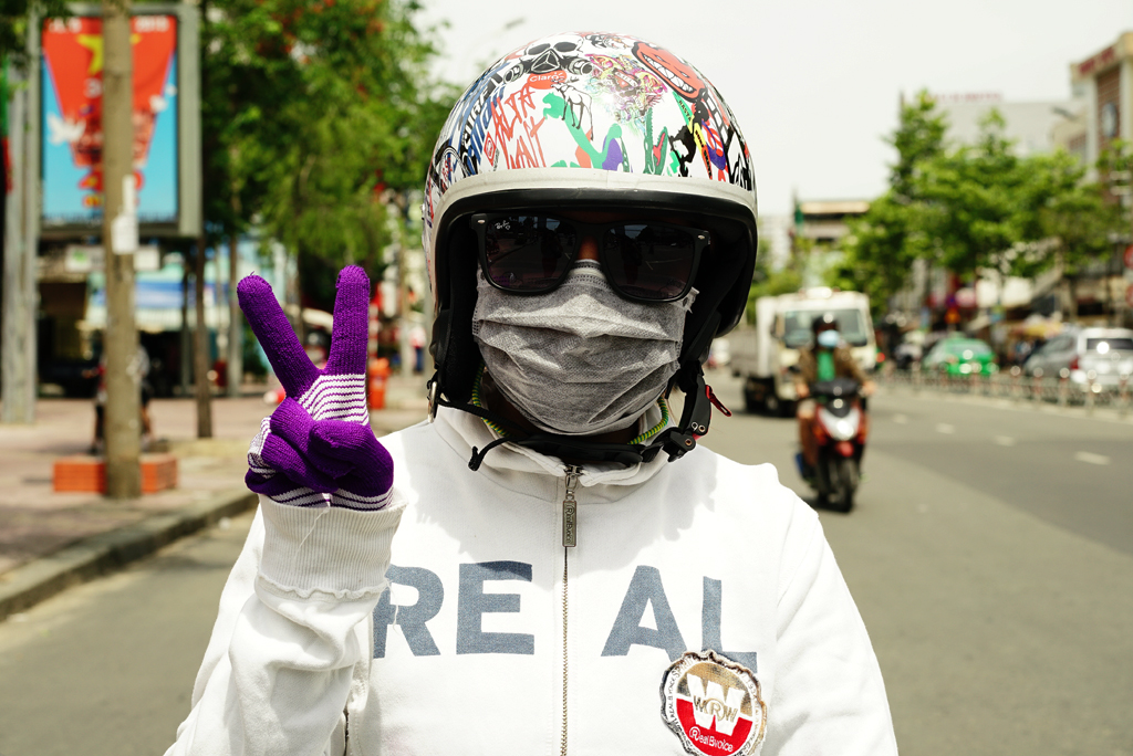 Teen-ager with gloves and white sweater %22Cover-up Style%22 driving on the streets of H.C.M.C., Vietnam, June 2015