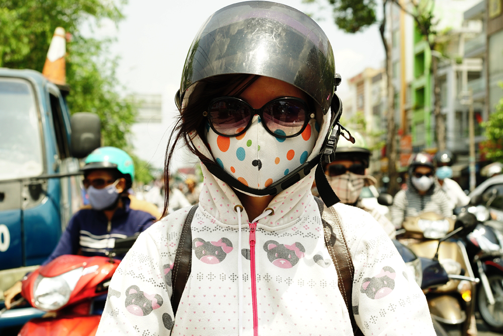 Teen-ager with simple decorated %22Cover-up Style%22 driving on the streets of H.C.M.C., Vietnam, June 2015