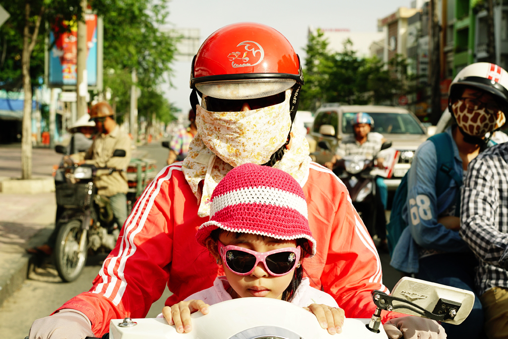 Woman with a colored %22Cover-up Style%22 and her daughter driving on the street of H.cC.M.C., Vietnam, June 2015