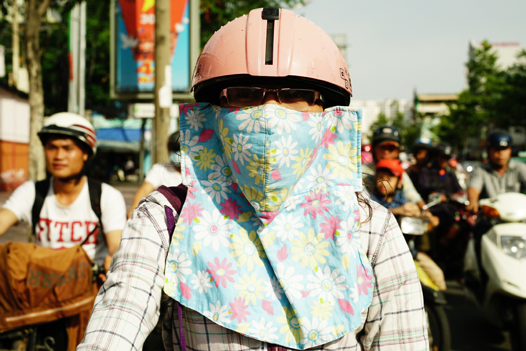 Woman with a large flowery mask %22Cover-up Style%22 driving on the streets of H.C.M.C, Vietnam, June 2015