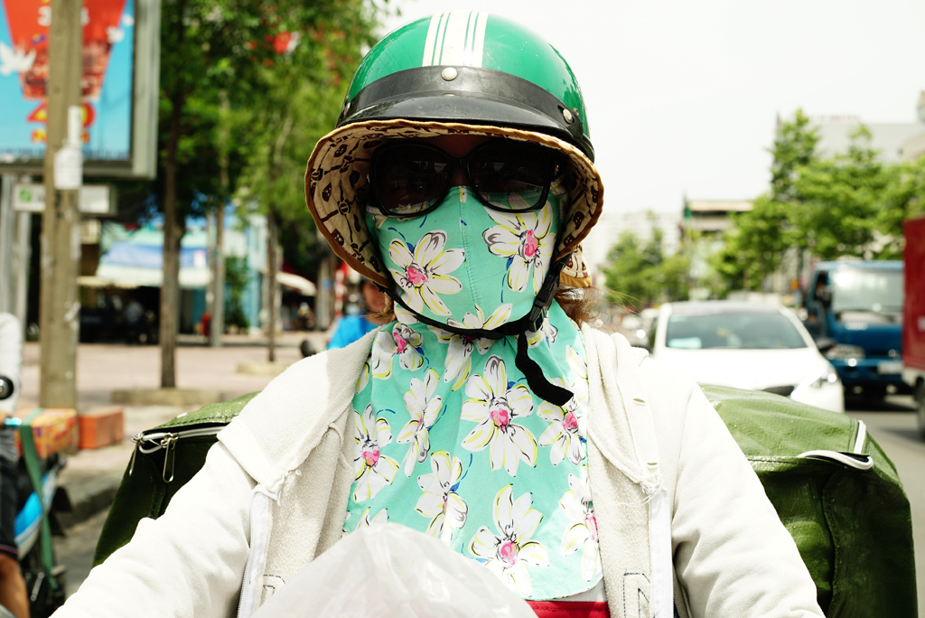 Woman with flowery mask %22Cover-up Style%22 driving on the streets of H.C.M.C.,Vietnam, June 2015
