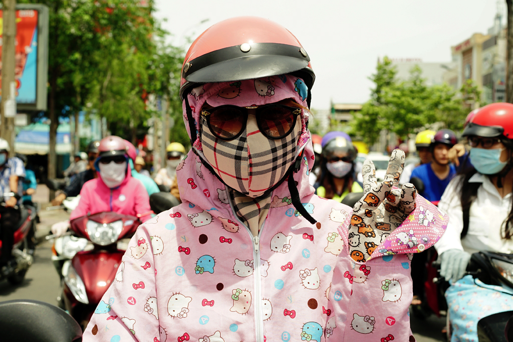 Young girl with Hello Kitty-Burberry %22Cover-up Style%22 driving on the streets of H.C.M.C., Vietnam, June 2015